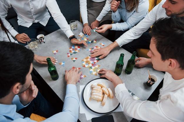 Вид сверху. отдых с игрой. празднование успешной сделки. молодые офисные работники сидят возле стола с алкоголем