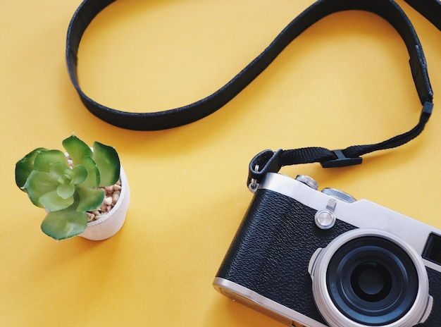 Top view of retro camera on yellow background.