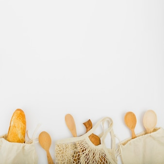 Top view of reusable bags with bread and wooden spoons