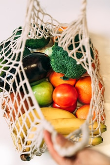 A top view of a reusable mesh shopping bag full of fruits and vegetables
