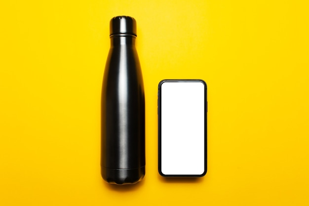Top view of reusable steel thermo water bottle and smartphone with mockup