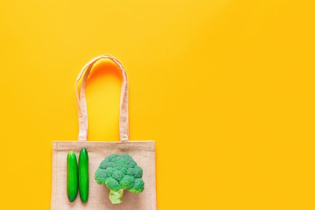 Top view of reusable textile shopping bag with fresh green vegetables on yellow background