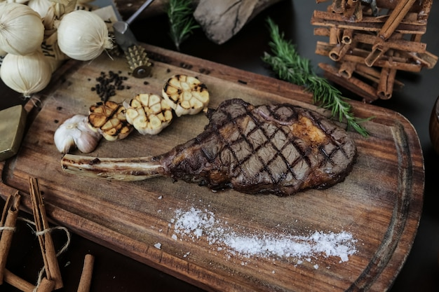 Top view rib steak with grilled garlic and salt on a stand with rosemary and cinnamon