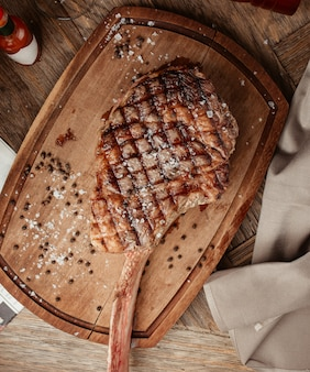 Top view of ribeye steak served on wooden board