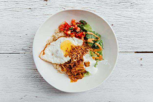 Top view of rice bowl toppings kimchi pork, organic fried egg, korean eggplant and salad.