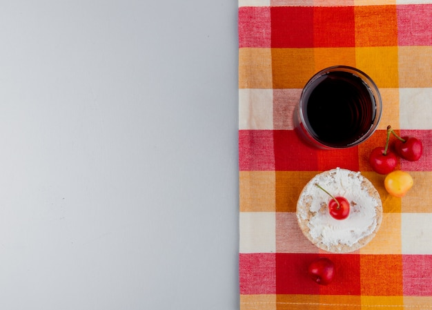Top view of rice cake with cream cheese and fresh ripe rainier cherries and a glass of cherry juice on plaid napkin on grey background with copy space