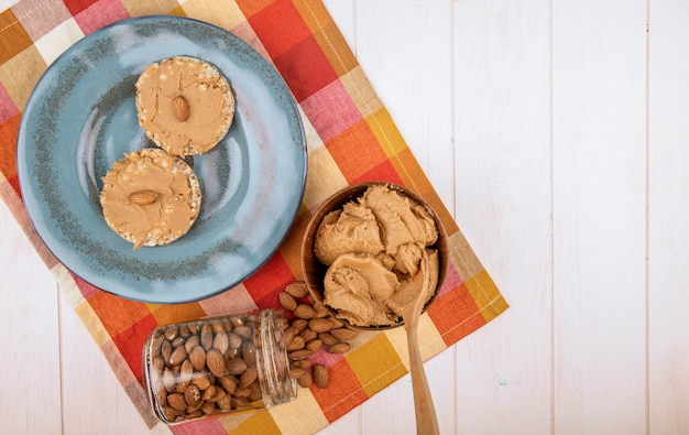 Top view of rice cereal cracker with peanut paste butter on blue ceramic plate almond scattered from a glass jar and a bowl with peanut butter on plaid table napkin on white wooden background wi