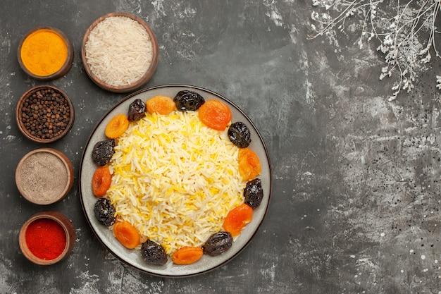 향신료 나무 가지 그릇 옆에 접시에 쌀 쌀과 말린 과일을 상위 뷰