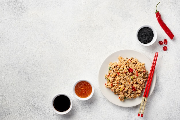 Top view rice with vegetables on plate chopsticks and soy sauce with copy space
