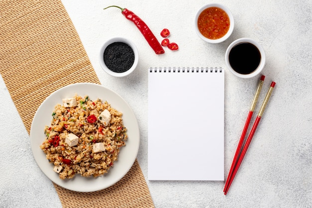 Top view rice with vegetables soy sauce and chopsticks with blank notebook