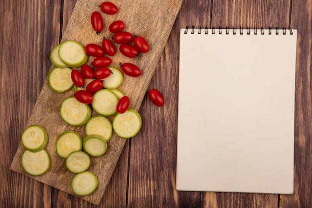 Vista dall'alto di zucchine tritate ricche di vitamine su una tavola di cucina in legno con pomodorini su un fondo di legno con lo spazio della copia