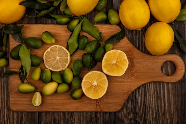 Vista dall'alto di frutti ricchi di vitamine come limoni e kinkan su una tavola da cucina in legno su una superficie di legno