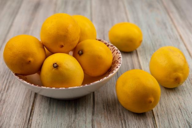 Vista dall'alto di limoni interi ricchi di vitamine su una ciotola con limoni isolati su una superficie di legno grigia