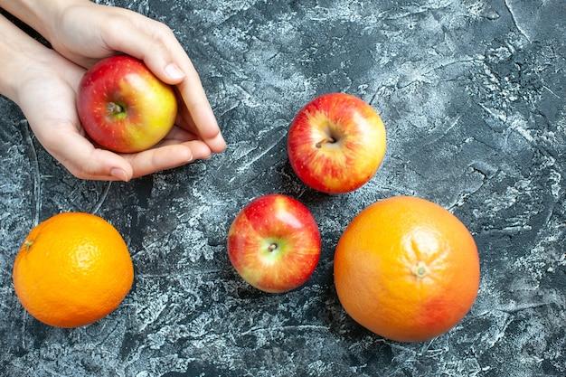 Вид сверху спелое яблоко в руках апельсины и яблоки на сером фоне свободного пространства