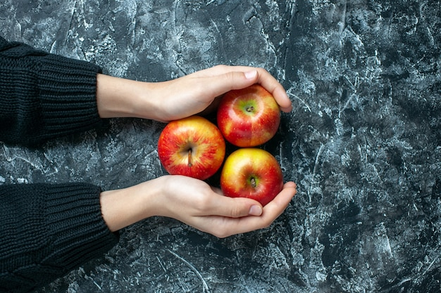 Top view ripe apples in female hands on grey background with copy place