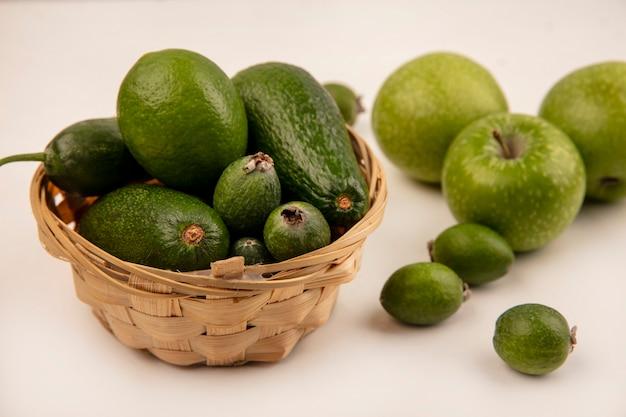 Vista dall'alto di avocado maturi con cetriolo su un secchio con mele verdi e feijoas isolati su una parete bianca