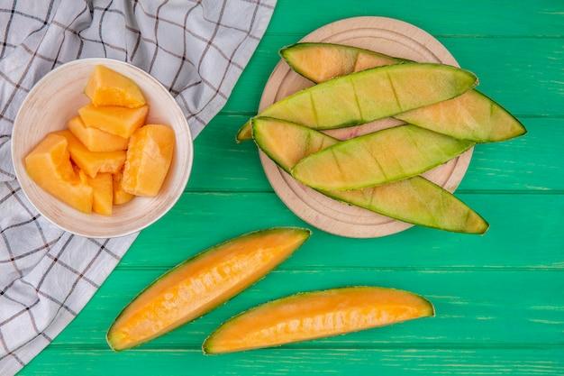 Vista superiore delle fette tritate mature di meloni su una ciotola sulla tovaglia controllata su superficie verde