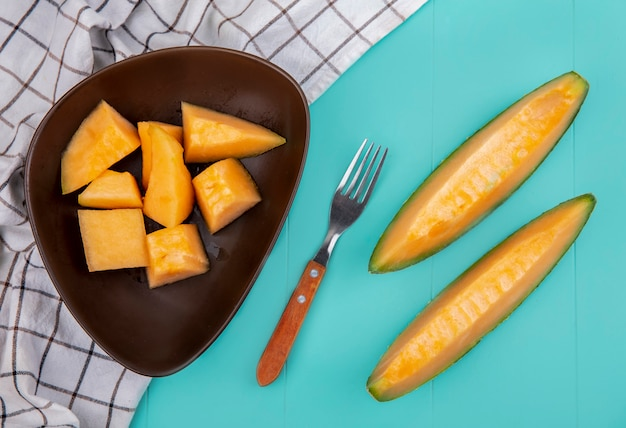 Top view of ripe delicious cantaloupe melon slices on a brown bowl with fork on checked tablecloth on blue surface