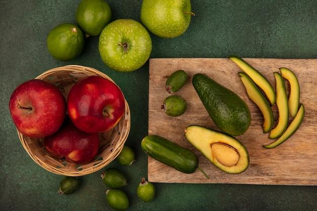 Vista dall'alto di avocado fresco maturo con fette su una tavola di cucina in legno con mele rosse su un secchio con feijoas di lime e mele verdi isolate su una superficie verde