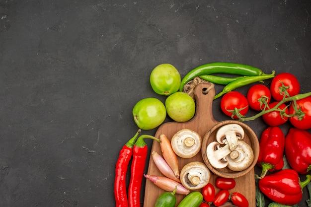 濃い灰色の背景にキノコと熟した新鮮な野菜の上面図