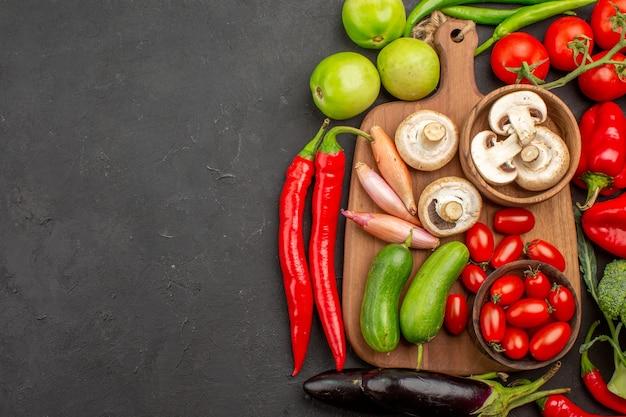 灰色の背景にキノコと熟した新鮮な野菜の上面図