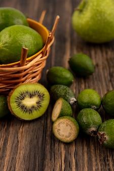 Vista dall'alto di limette mature su un secchio con mele verdi kiwi feijoas isolato su una parete in legno