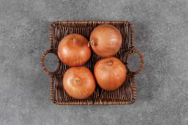 Top view of ripe onions in basket .