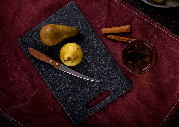 Top view of ripe pears on a black board with kitchen knife and a glass of juice on purple tablecloth
