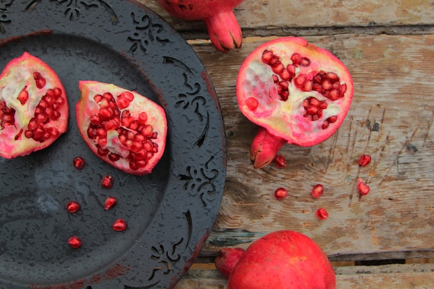 Top view of ripe pomegranate fruit on antique plate