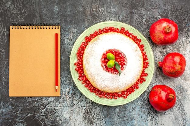 上面図熟したザクロケーキのノートブック鉛筆プレートの横にある熟した赤いザクロ