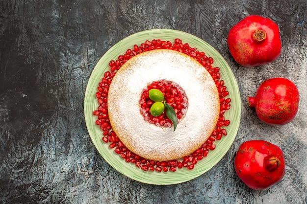 Vista dall'alto melograni maturi melograni rossi maturi accanto al piatto di torta