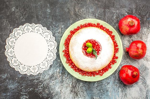 Vista dall'alto melograni maturi tre melograni accanto al piatto di torta e centrino di pizzo bianco