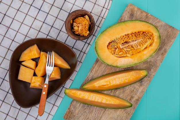 Top view of ripe sweet cantaloupe melon slices on a wooden kitchen surface with melon slices on a brown bowl with knife on a checked tablecloth on blue surface