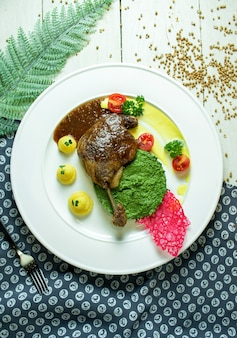Top view of roast duck leg with avocado sauce and mashed potatoes with cherry tomatoes on a white plate