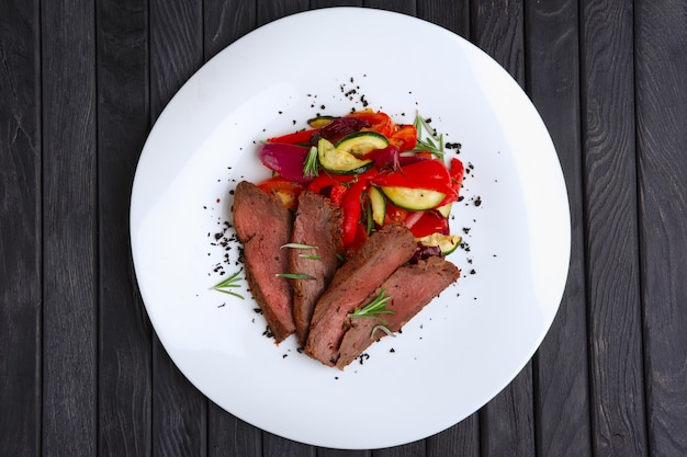 Top view of roasted beef cutted on slices with grilled bell pepper, zucchini, onion and fresh rosemary