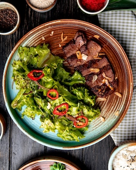 Top view of roasted beef with lettuce and red chili pepper on a plate on wood
