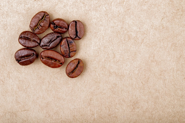 Top view of roasted coffee beans isolated brown paper texture background with copy space