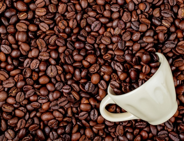 Top view of roasted coffee beans scattered from a ceramic cup on coffee beans background