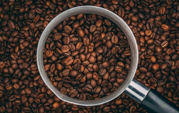 Top view of roasted coffee beans in steel cup