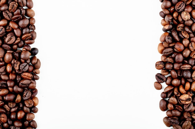 Top view of roasted coffee beans on white background with copy space
