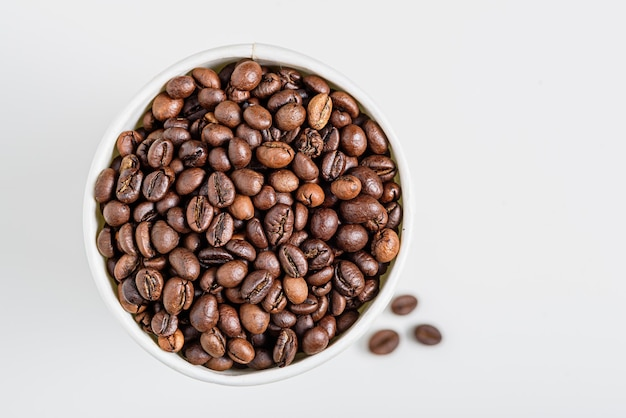 Top view roasted coffee beans in white cup on white