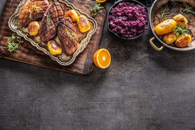 Top view of a roasted duck breasts with oranges, roasted potatoes and red cabbage, on a dark surface.