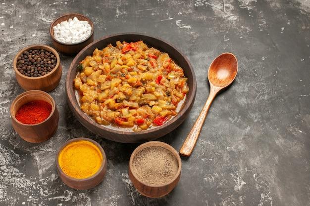Vista dall'alto di insalata di melanzane arrosto nella ciotola e diverse spezie in ciotole foglia di cucchiaio di legno sulla superficie scura