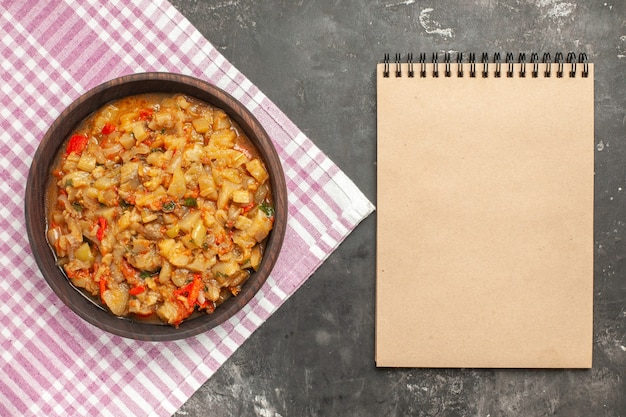 Top view of roasted eggplant salad in bowl a notebook on dark surface