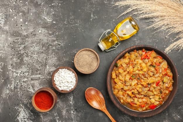 Vista dall'alto di insalata di melanzane arrosto nella ciotola, bottiglia di olio, cucchiaio di legno e diverse spezie in ciotole sulla superficie scura