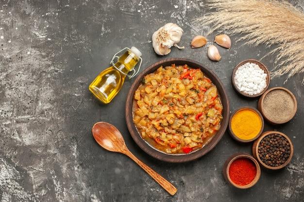 Vista dall'alto di insalata di melanzane arrosto nella ciotola, bottiglia di olio, cucchiaio di legno e diverse spezie in ciotole aglio sulla superficie scura