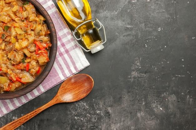 Vista dall'alto di insalata di melanzane arrosto in una ciotola di olio e cucchiaio di legno sulla superficie scura