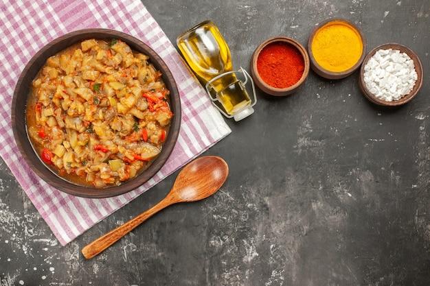 Vista dall'alto di insalata di melanzane arrosto nella ciotola, olio, cucchiaio di legno e diverse spezie sulla superficie scura