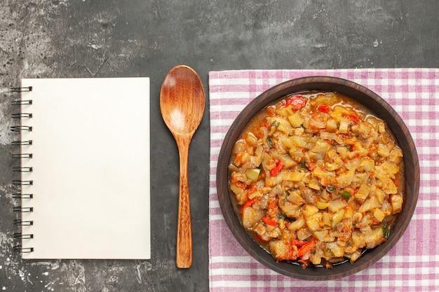 Vista dall'alto di insalata di melanzane arrosto in una ciotola un cucchiaio di legno un blocco note sulla superficie scura