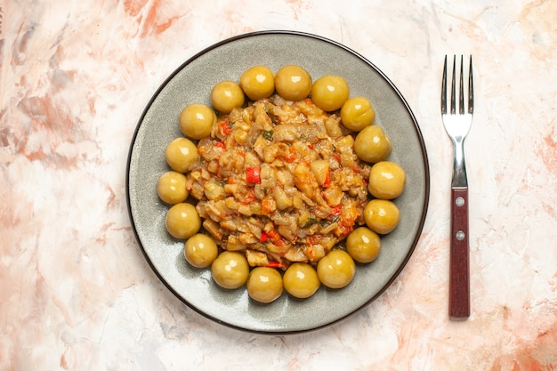 Top view of roasted eggplant salad and pickled plums on plate fork on nude surface